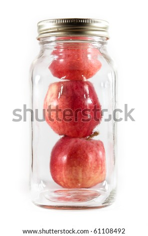 Three red gala apples behind a tall glass mason jar for canning on a white isolated background. - stock photo