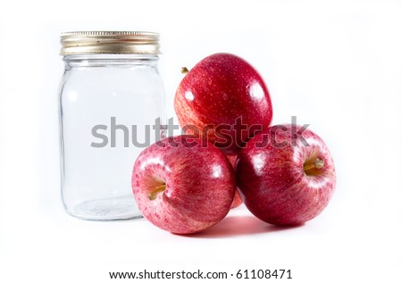 three red gala apples piled beside a glass mason jar with metal lid on a white isolated background. - stock photo