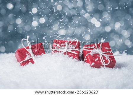 Three red gift boxes in snow on abstract background - stock photo