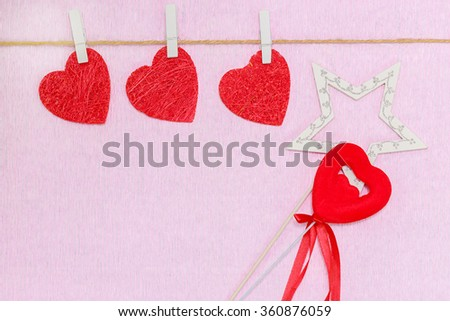 Three red hearts hang on clothespin. White star and red heart on pink background - stock photo