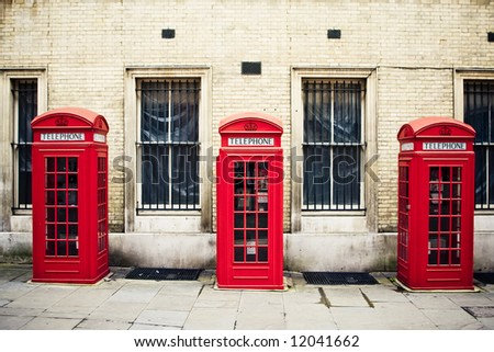 Three red phone boxes over grunge wall background - stock photo