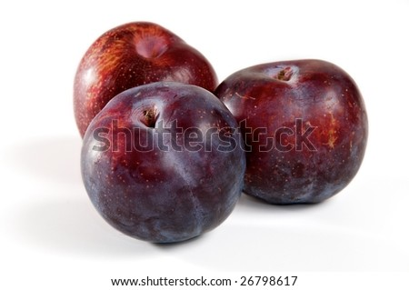 Three red plums on a white background. - stock photo