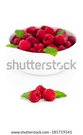 Three red raspberries with fresh mint leaves in front of white bowl with raspberries - isolated on white background - stock photo