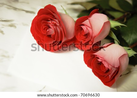 three red roses and a letter on the marble table - stock photo