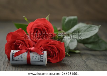 three red roses and bunch of dollar bills, Shallow DOF - stock photo