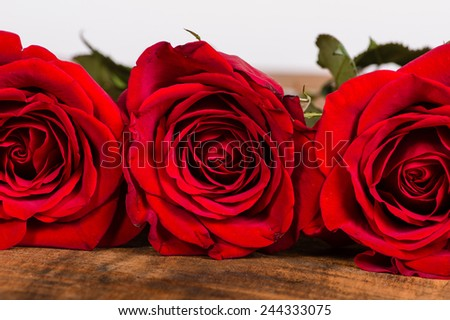 Three red roses in a row on wooden table - stock photo