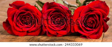 Three red roses on wooden table tight frame - stock photo