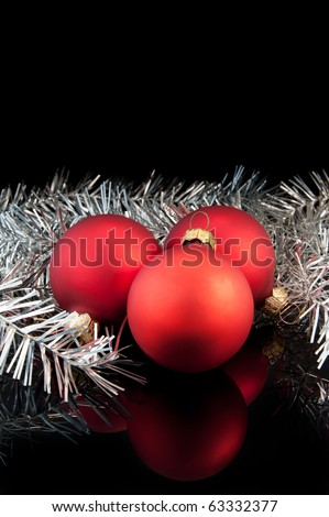 Three red satin Christmas balls with silver decoration on black background - stock photo