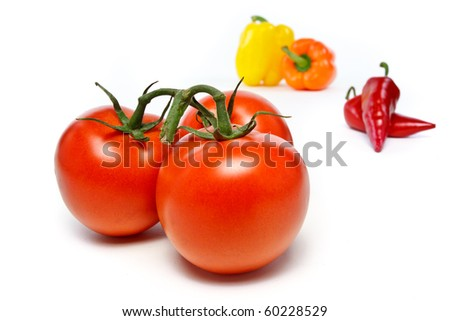 Three red tomatoes two bell peppers and chili peppers - stock photo