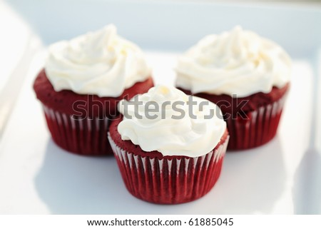 Three red velvet cupcakes on a white dish with extreme shallow DOF. - stock photo