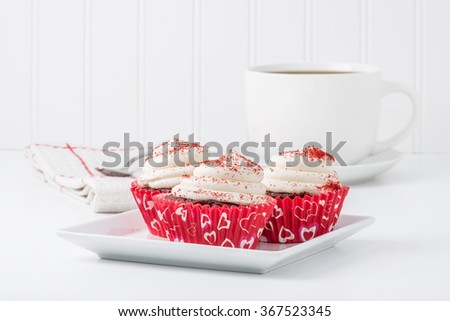 Three red velvet cupcakes served with a cup of coffee. - stock photo