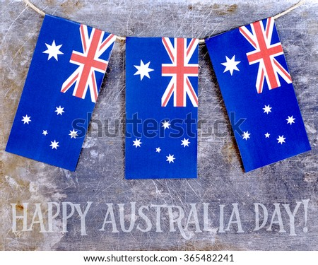 Three red, white and blue Australian flags suspended from a twine rope in front of a grungy, steel background for Australia Day on January 26.  Thematic message across bottom of horizontal image. - stock photo