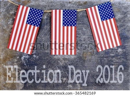 Three red, white and blue USA flags suspended from a twine rope in front of a grungy, steel background for any election day in the United States.  Thematic message across bottom of horizontal image. - stock photo