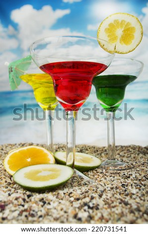 three refreshing red yellow green fruity cocktails with lime slice on the sand with the sea beach ocean in the background - stock photo