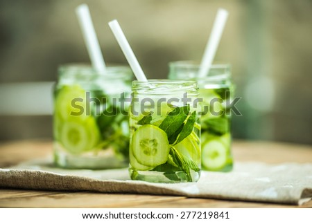 Three retro glass jars of lemonade with cucumber and mint on wooden table - stock photo