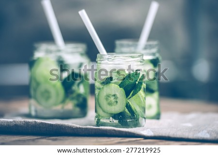 Three retro glass jars of lemonade with cucumber and mint on wooden table. Toned image - stock photo