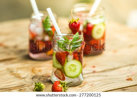 Three retro glass jars of lemonade with  strawberries, cucumber and mint on wooden table - stock photo