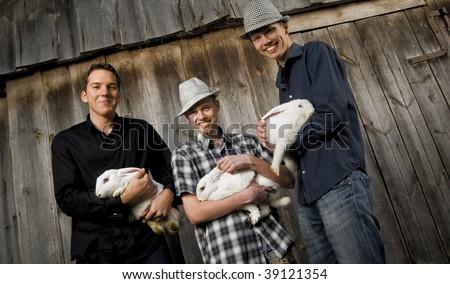 Three retro men's with bunnies in hands - stock photo