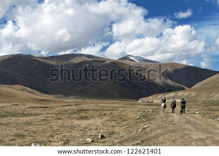 Three riders on the mountain road - stock photo