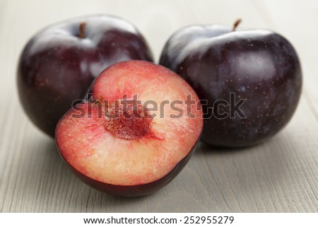three ripe black plums on wood table - stock photo
