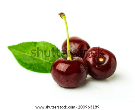 Three ripe cherries with leaf isolated on white