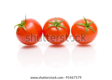 three ripe cherry tomato with reflection on white background close-up - stock photo