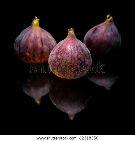 three ripe purple fig fruits isolated on black background, with reflection - stock photo