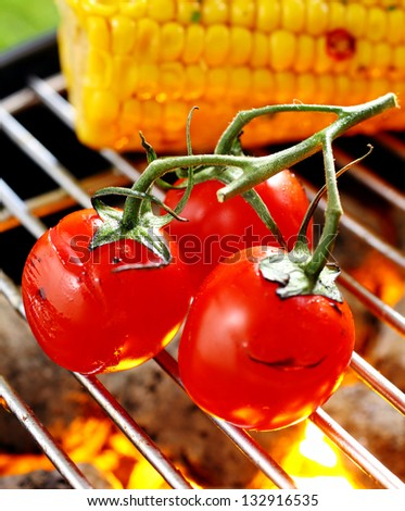 Three ripe red cherry tomatoes still attached to the vine balanced on a barbecue grid grilling over a fire - stock photo