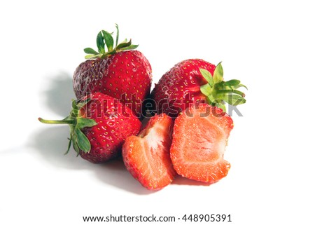 Three ripe red strawberries with cut strawberry on a white background, isolated - stock photo