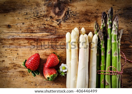 Three ripe red strawberries with stemmed floret along side of bundled white and green asparagus on wooden table - stock photo