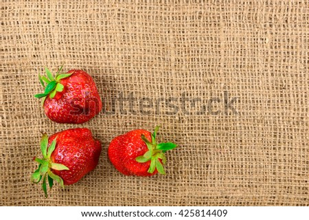Three ripe strawberries lie on the fabric. Design element