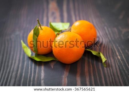 Three ripe tangerine on a dark wooden table - stock photo