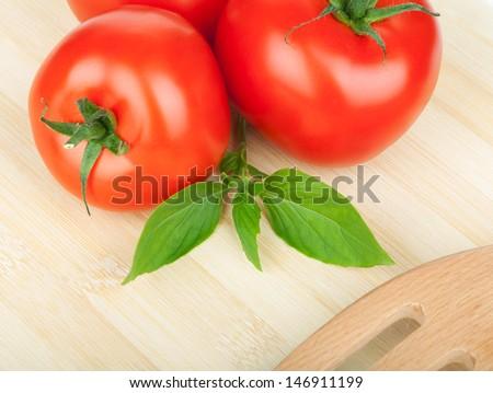 Three ripe tomatoes and basil on cutting board - stock photo