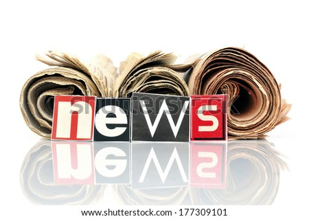Three rolled newspapers with lettering NEWS in front - stock photo