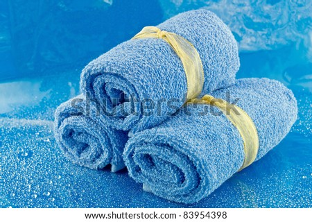 Three rolled up blue bath towels on a blue background. - stock photo