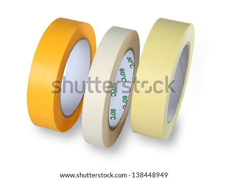 Three rolls of narrow masking tape, yellow, white and brown, standing at his side, isolated on a white background. - stock photo