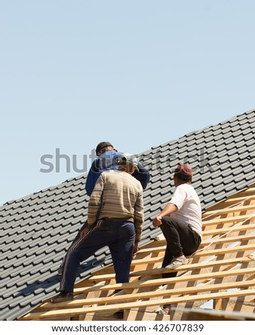 three roofers do roof metal tile - stock photo