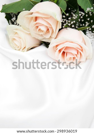 Three roses on a white silk background