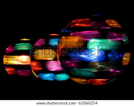 Three rotating disco light-balls in a row on a black background - stock photo