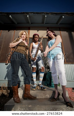 Three rough women on a house step - stock photo
