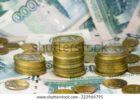 Three rows of coins with paper money on the background