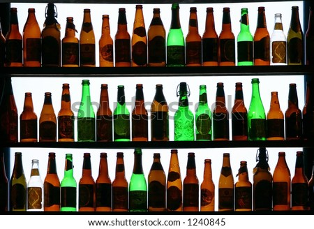 three rows of liquor and beer bottles backlit - stock photo