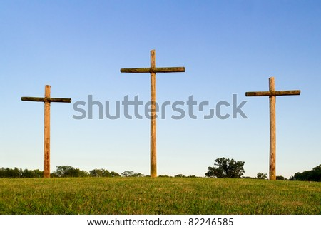 Three rugged wooden crosses standing on a green hill with blue sky