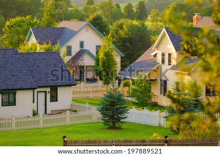 Three rural homes with white picket fences in Stowe Vermont, USA - stock photo