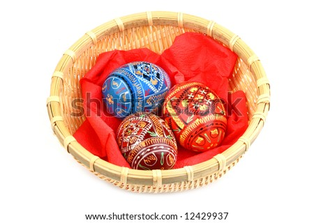 three russian tradition easter eggs in yellow basket over white