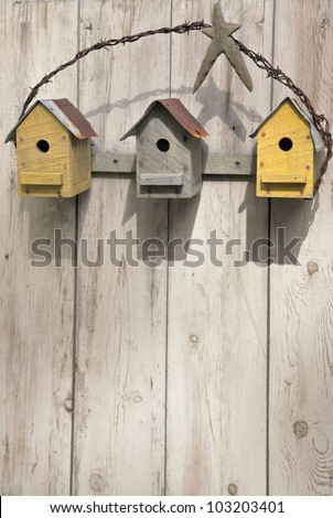 Three rustic birdhouses hanging on a wooden fence. - stock photo