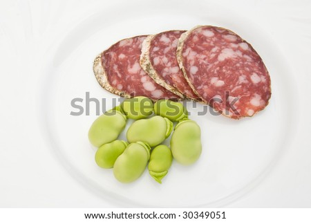 Three salami slices with fava beans on a white dish - stock photo