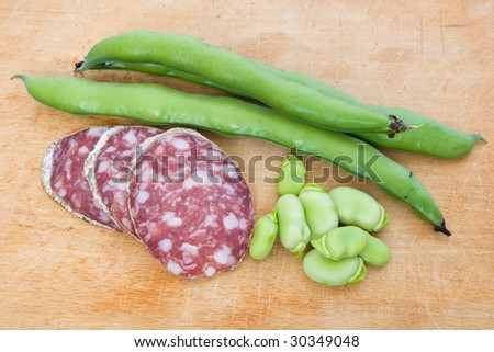 Three salami slices with fava beans on a wood chopping board - stock photo