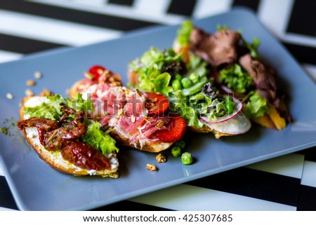 three sandwiches with bacon and fresh vegetables on vintage  blue plate. Close-up. - stock photo