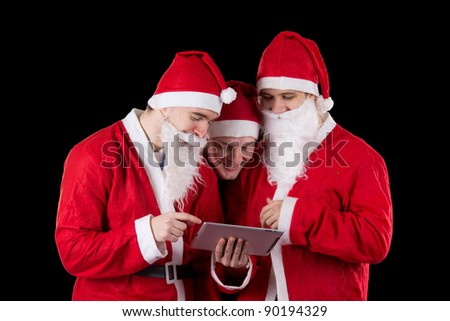 Three santa claus sending email on tablet PC - stock photo
